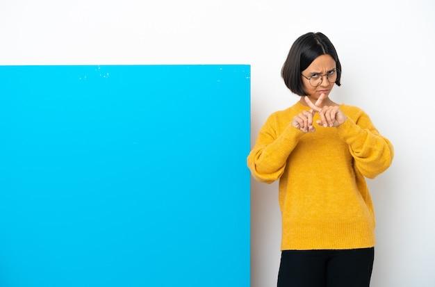 행동을 막기 위해 그녀의 손으로 중지 제스처를 만드는 흰색 배경에 고립 된 큰 파란색 현수막을 가진 젊은 혼합 된 인종 여자