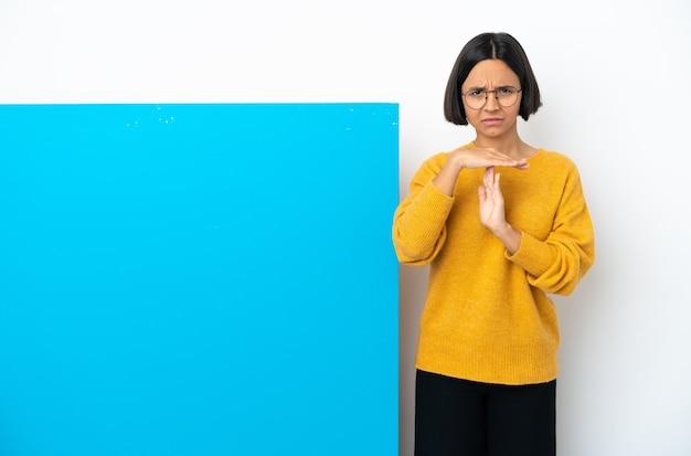 시간 초과 제스처를 만드는 흰색 배경에 고립 된 큰 파란색 현수막을 가진 젊은 혼혈 여자