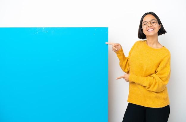 Молодая женщина смешанной расы с большим синим плакатом, изолированным на белом фоне, указывая пальцем в сторону и представляя продукт