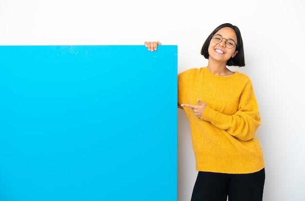 Молодая женщина смешанной расы с большим синим плакатом на белом фоне, указывая пальцем в сторону