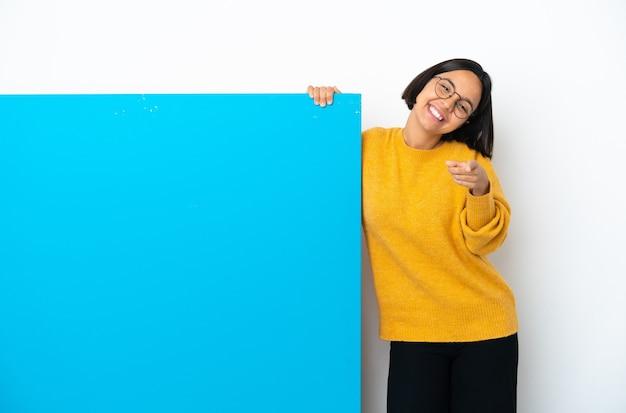 幸せな表情で正面を向いている白い背景で隔離の大きな青いプラカードを持つ若い混血の女性