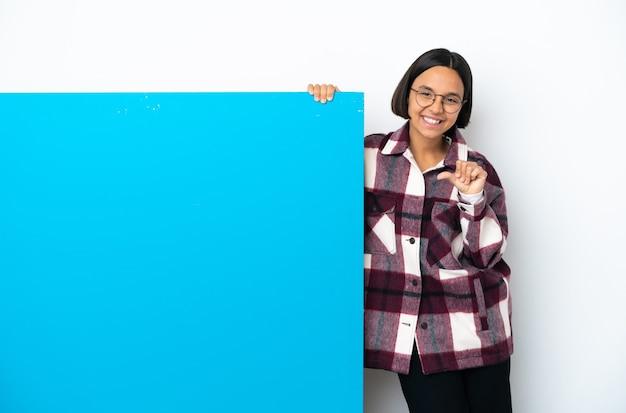 제품을 제시하기 위해 측면을 가리키는 흰색 배경에 고립 된 큰 파란색 현수막을 가진 젊은 혼혈 여자