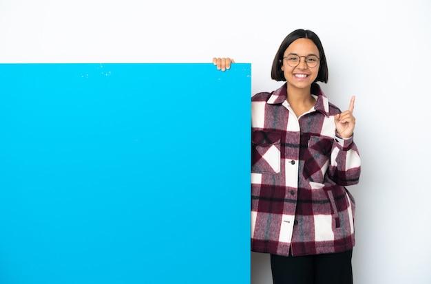 좋은 아이디어를 가리키는 흰색 배경에 고립 된 큰 파란색 현수막을 가진 젊은 혼혈 여자