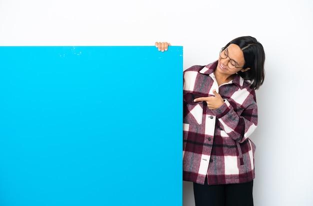 Молодая женщина смешанной расы с большим синим плакатом на белом фоне, указывая указательным пальцем - отличная идея