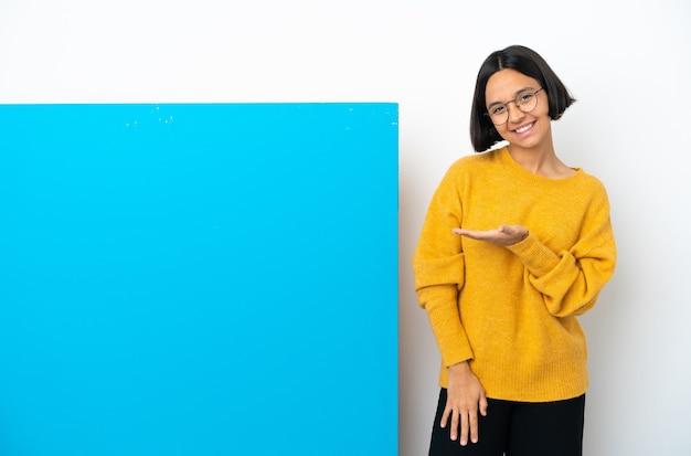 に向かって笑顔を見ながらアイデアを提示する白い背景で隔離の大きな青いプラカードを持つ若い混血の女性