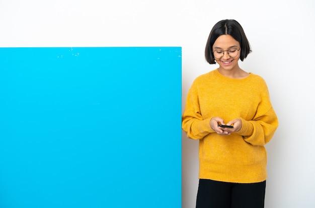Молодая женщина смешанной расы с большим синим плакатом, изолированным на белом фоне, отправляет сообщение с мобильного телефона