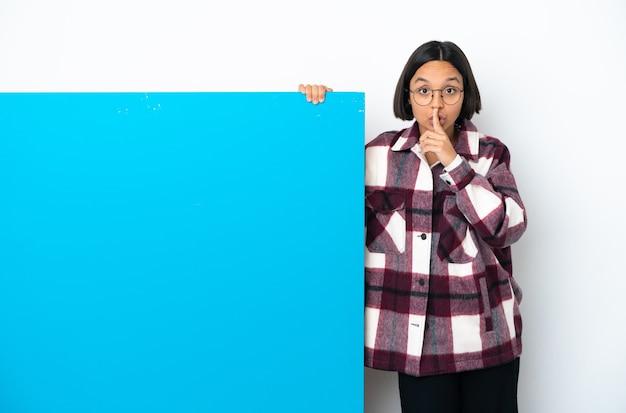 입에 손가락을 넣어 침묵 제스처의 기호를 보여주는 흰색 배경에 고립 된 큰 파란색 현수막을 가진 젊은 혼혈 여자 프리미엄 사진