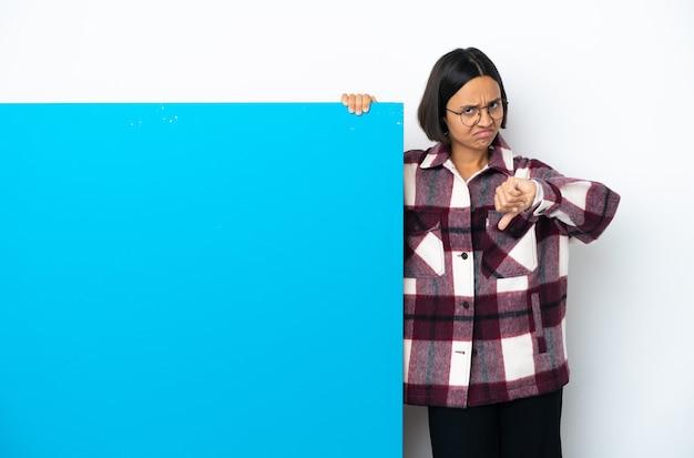 부정적인 표현으로 아래로 엄지 손가락을 보여주는 흰색 배경에 고립 된 큰 파란색 현수막을 가진 젊은 혼합 된 인종 여자