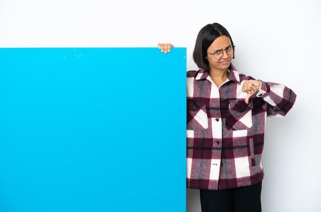 두 손으로 엄지손가락을 아래로 보여주는 흰색 배경에 고립 된 큰 파란색 현수막을 가진 젊은 혼혈 여성