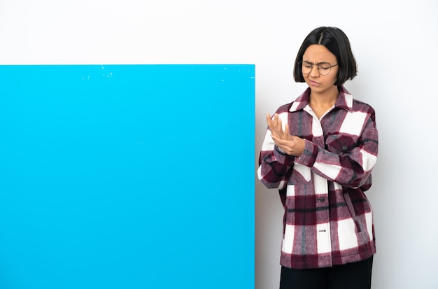 손에 통증을 앓고 흰색 배경에 고립 된 큰 파란색 현수막을 가진 젊은 혼합 된 인종 여자