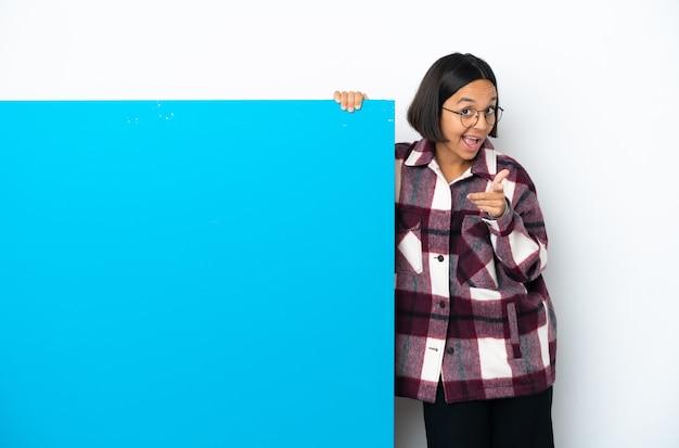 白い背景に分離された大きな青いプラカードを持つ若い混血の女性は驚いて正面を指しています