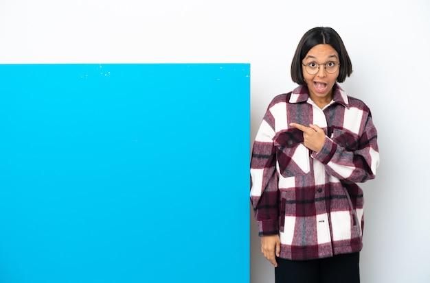 白い背景で隔離の大きな青いプラカードを持つ若い混血の女性は驚いて、側を指しています