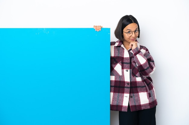 Молодая женщина смешанной расы с большим синим плакатом на белом фоне думает Premium Фотографии