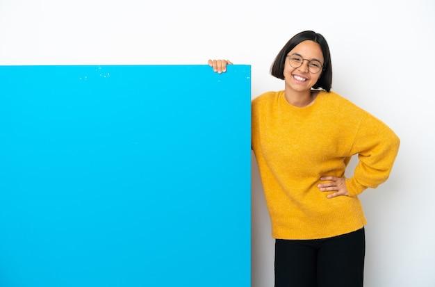 Молодая женщина смешанной расы с большим синим плакатом изолирована на белом фоне со скрещенными руками и смотрит вперед