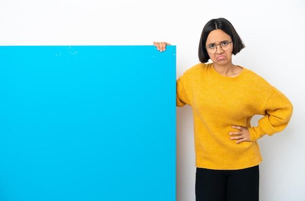悲しい表情で白い背景に分離された大きな青いプラカードを持つ若い混血の女性