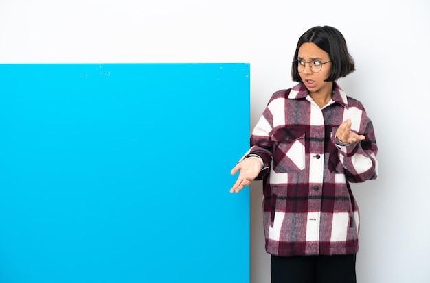 側を見ながら驚きの表情で白い背景に分離された大きな青いプラカードを持つ若い混血女性