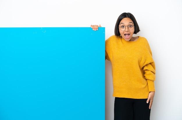 驚きの表情で白い背景に分離された大きな青いプラカードを持つ若い混血の女性