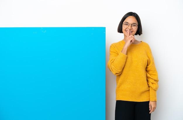 입에 손가락을 넣어 침묵 제스처의 기호를 보여주는 고립 된 큰 파란색 현수막을 가진 젊은 혼합 된 인종 여자
