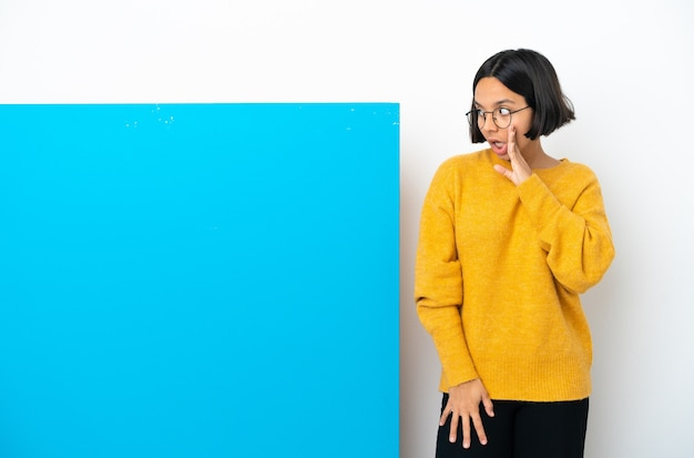 大きな青いプラカードを持った若い混血の女性が、横を見ながら驚きのジェスチャーで何かをささやく孤立した