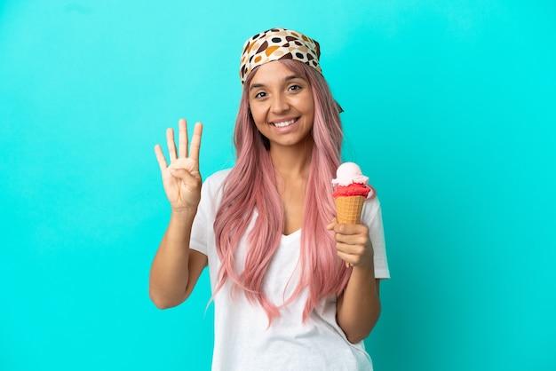 Молодая женщина смешанной расы с мороженым корнет, изолированные на синем фоне, счастлива и считает четыре пальцами