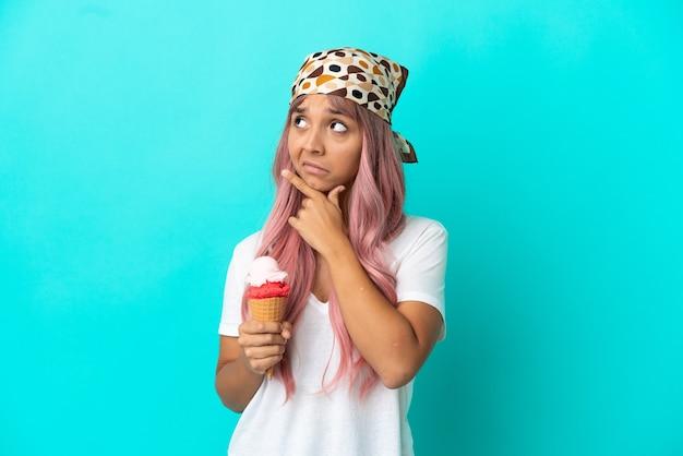 Молодая женщина смешанной расы с мороженым корнет, изолированные на синем фоне, сомневаясь