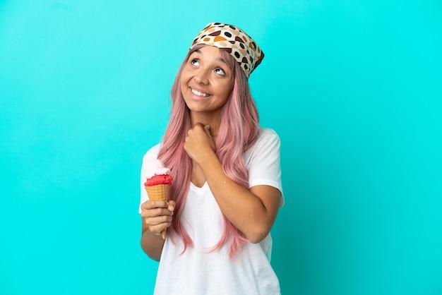 笑顔で見上げる青い背景に分離されたコルネットアイスクリームと若い混血の女性