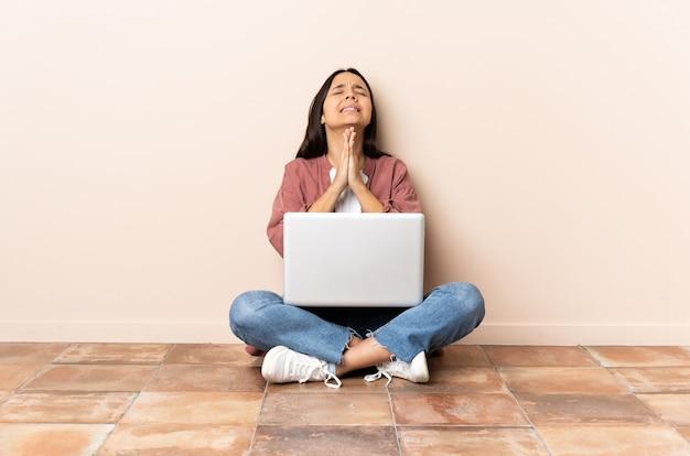 Молодая женщина смешанной расы с ноутбуком, сидя на полу, держит ладонь вместе. человек о чем-то просит