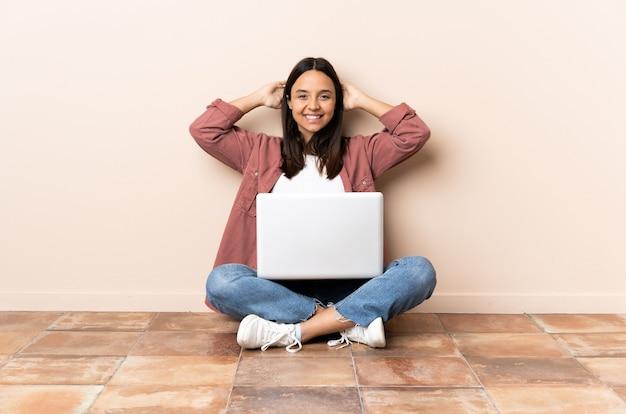 笑って床に座っているラップトップを持つ若い混血の女性
