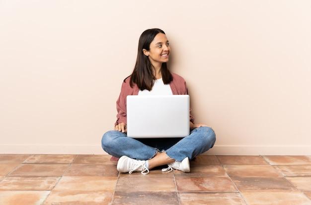 측면을 찾고 바닥에 앉아 노트북으로 젊은 혼혈 여자