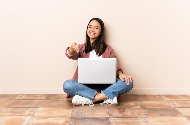 握手して床に座っているラップトップを持つ若い混血の女性