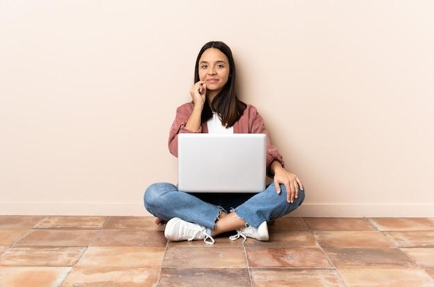 침묵 제스처의 표시를 보여주는 바닥에 앉아 노트북과 젊은 혼혈 여자