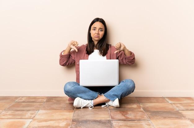 Молодая женщина смешанной расы с ноутбуком сидит на полу, показывая большой палец вниз