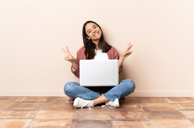 양손으로 승리 기호를 보여주는 바닥에 앉아 노트북으로 젊은 혼혈 여자