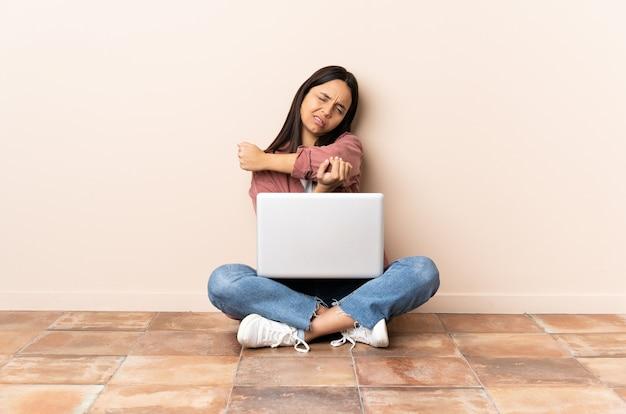 팔꿈치에 통증이 함께 바닥에 앉아 노트북과 젊은 혼혈 여자