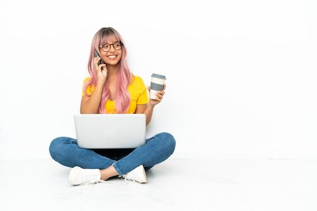 Молодая женщина смешанной расы с ноутбуком с розовыми волосами сидит на полу на белом фоне, держа кофе на вынос и мобильный