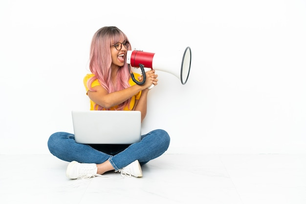 Молодая женщина смешанной расы с ноутбуком с розовыми волосами сидит на полу, изолированном на белом фоне, кричит в мегафон