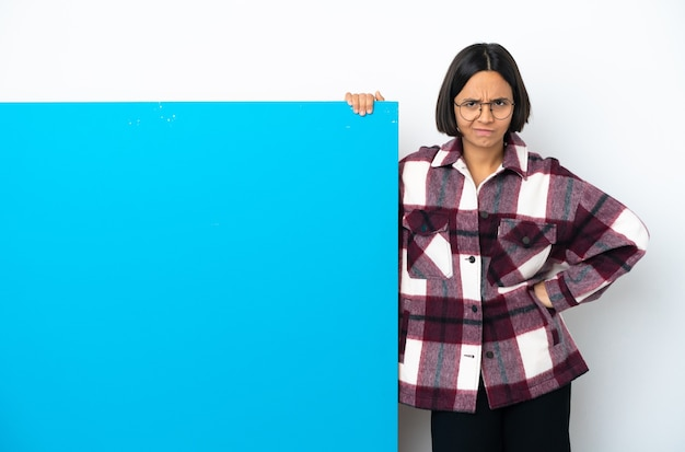 Young mixed race woman with a big blue placard isolated on white background angry