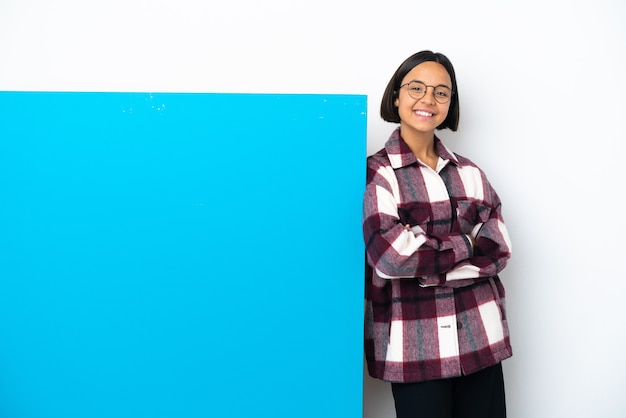 Young mixed race woman with a big blue placard isolated on white background keeping the arms crossed in frontal position