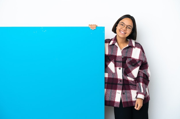 Young mixed race woman with a big blue placard isolated on white background laughing