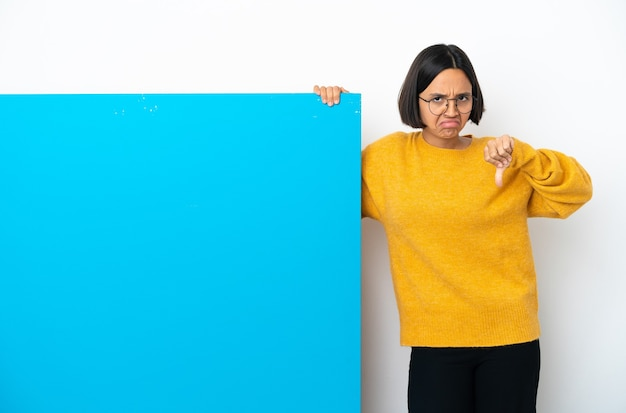 Young mixed race woman with a big blue placard isolated on white background making good-bad sign. undecided between yes or not