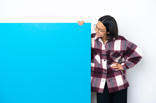 Young mixed race woman with a big blue placard isolated on white background thinking an idea while looking up