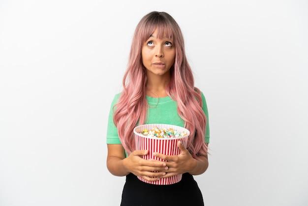 Молодая женщина смешанной расы с розовыми волосами ест попкорн на белом фоне и смотрит вверх