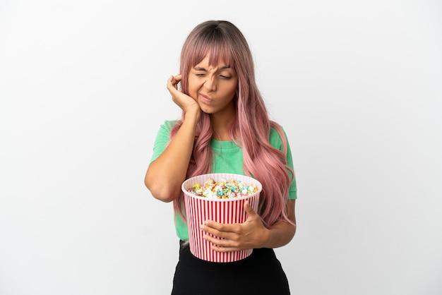 Молодая женщина смешанной расы с розовыми волосами ест попкорн на белом фоне разочарована и закрывает уши