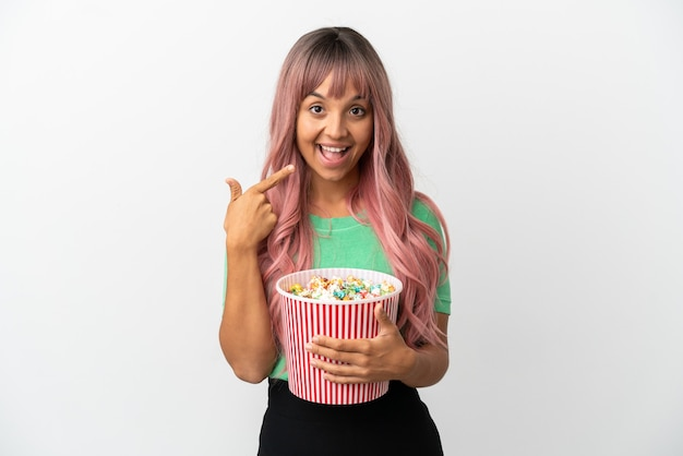 Молодая женщина смешанной расы с розовыми волосами ест попкорн на белом фоне, показывая большой палец вверх
