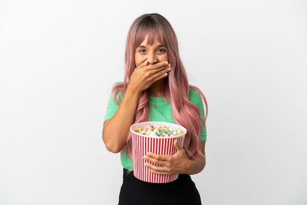Молодая женщина смешанной расы с розовыми волосами, едящая попкорн на белом фоне, счастливая и улыбающаяся, прикрывая рот рукой