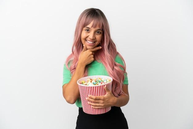 Молодая женщина смешанной расы с розовыми волосами ест попкорн на белом фоне счастлива и улыбается