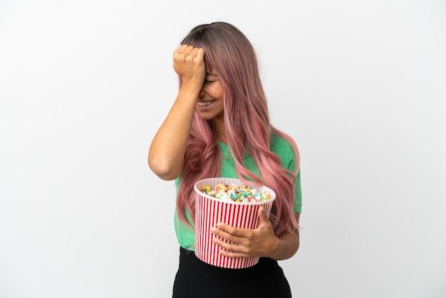 白い背景で隔離のポップコーンを食べるピンクの髪を持つ若い混血の女性は何かを実現し、解決策を意図しています