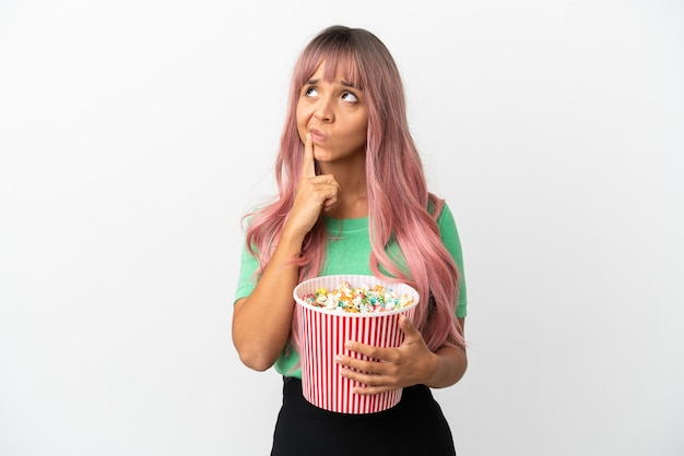 Молодая женщина смешанной расы с розовыми волосами ест попкорн на белом фоне, сомневаясь, глядя вверх