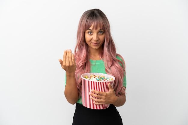 Молодая женщина смешанной расы с розовыми волосами ест попкорн на белом фоне, приглашая прийти с рукой. счастлив что ты пришел