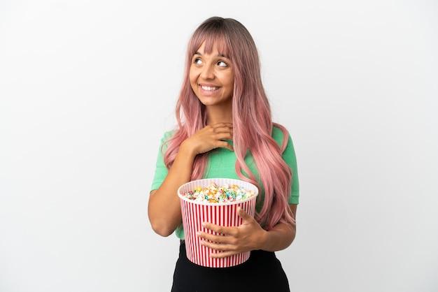 笑顔で見上げる白い背景で隔離のポップコーンを食べるピンクの髪を持つ若い混血の女性